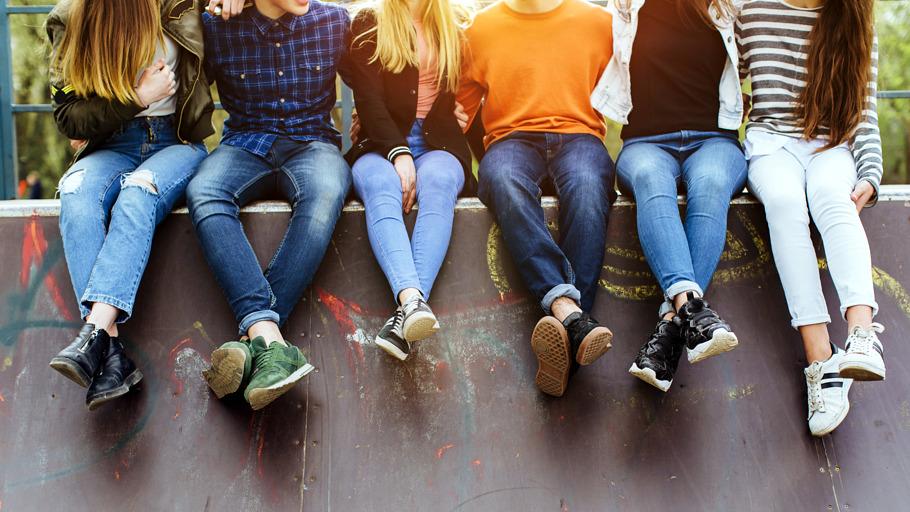 Groupe de jeunes gens assis sur un muret
