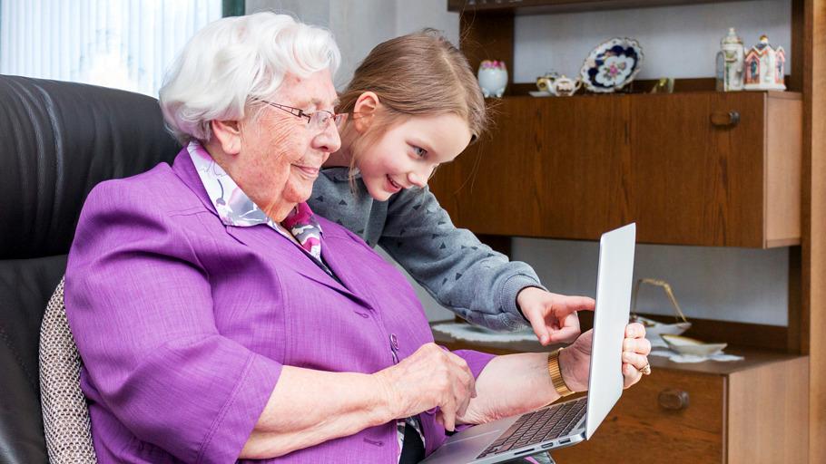 Une personne agée est aidée par une enfant pour utiliser un ordinateur