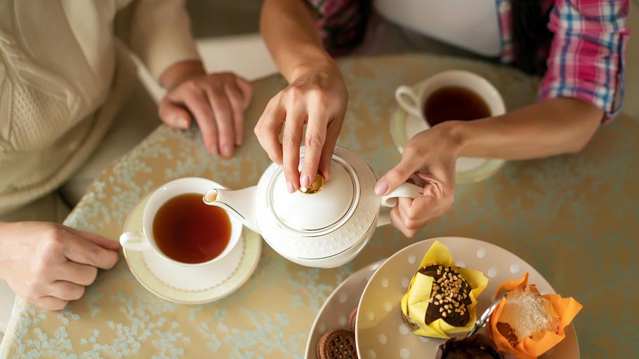 Deux personnes prenant le thé et des gateaux