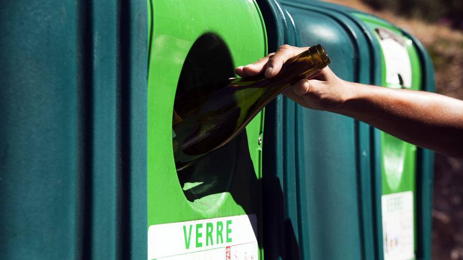 Bouteille en verre jetée dans un conteneur de recyclage verre